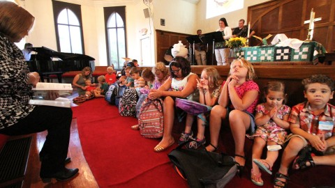 Blessing the Backpacks - photo by Moses Leos III, Hays Free Press, Aug. 26, 2015